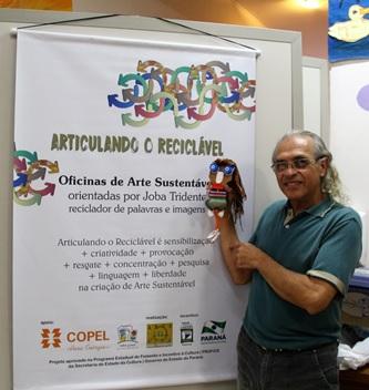 Professor Joba Tridente com o cartaz da oficina e a boneca MaryLinda, criada em 2010  Foto: Larissa Miglioli