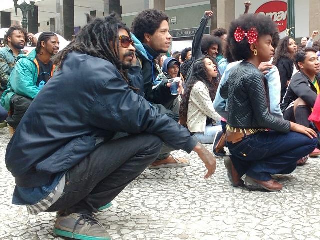 Marcha - Manifestantes se sentam para ouvir gritos de guerra